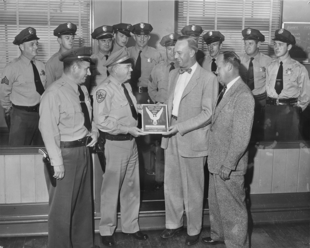 "Pacific Grove, CA  Police Department group photo, receiving a plaque from the National Safety Council, ""National Traffic Safety Contest Honor Roll 1951"".   Plaque appears to be presented by a CHP Captain.  Image Courtesy of Gene Green."