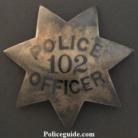 Officer J. W. Slagle wearing badge No. 102.  Badge is sterling and dated 10-14-19.