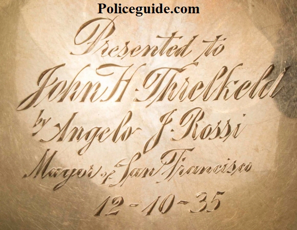 Reverse of badge showing presentation:  Presented to John H. Threlkeld by Angelo F. Rossi Mayor of San Francisco 12-10-35.